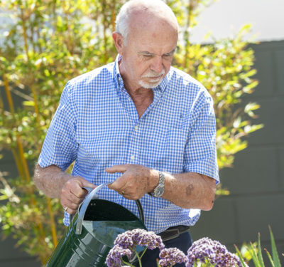 Eldery resident watering the gardens at The Richardson