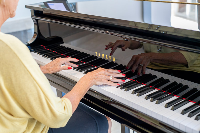 Elderly woman playing music on the piano